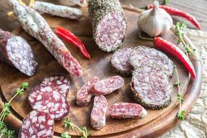 fatias de saucisson, fuet e salame na placa de madeira