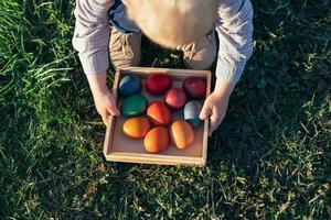 garoto carregando uma caixa de madeira com ovos de páscoa ao pôr do sol foto