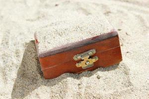 baú do tesouro enterrado na areia foto