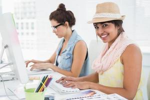 colegas de trabalho digitando no teclado a sorrir foto