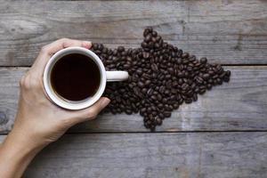 femininas mãos segurando uma xícara com grãos de café na mesa de madeira foto