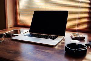 netbook com tablet digital deitado sobre uma mesa de escritório foto