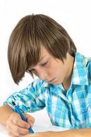 menino de escola com lápis trabalha concentrado, isolado no branco foto