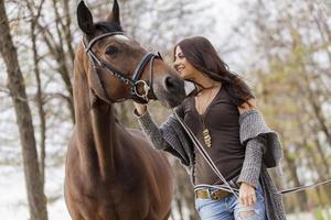 jovem mulher com um cavalo foto