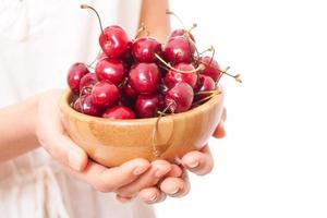 tigela de cerejas nas mãos das mulheres foto