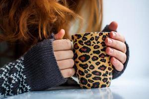 mulher segurando um copo de bebida quente foto