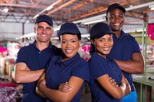 colegas de fábrica têxtil com braços cruzados foto