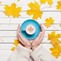 mãos femininas segurando uma xícara de café na mesa de madeira. foto