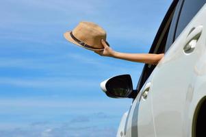 mulher feliz mostra chapéu de sol da janela do carro foto
