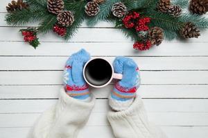 menina segurando a xícara de café perto de galhos de pinheiro foto