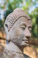 cabeça de Buda em frente a parede velha foto