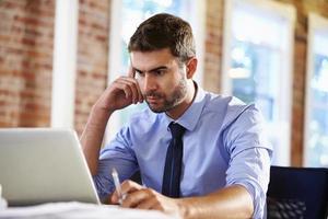 homem trabalhando no laptop no escritório contemporâneo foto