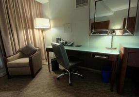 sala de estudo com escrivaninha poltrona lâmpada e espelho