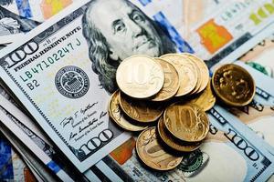 moedas de rublos russos nas notas de dólares foto