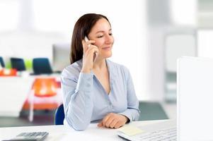 empresária falando pelo smartphone no escritório foto