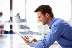 retrato de homem no escritório usando tablet