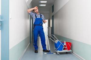 trabalhador masculino cansado, limpeza, corredor escritório foto