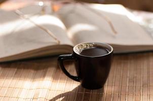 xícara de café, ao lado de um livro aberto foto