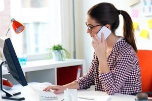 mulher jovem e bonita usando seu laptop no escritório. foto