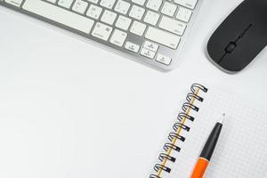 caderno em branco com caneta e teclado no escritório foto