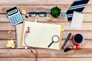 material de escritório e café na mesa, local de trabalho foto