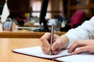 homem escreve algo em um papel branco. escritório foto