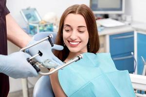 paciente jovem, dentista visitante no consultório odontológico foto