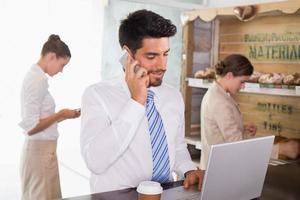 empresário usando telefone celular e laptop na cantina do escritório foto