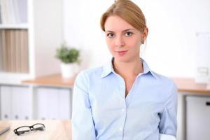 mulher de negócios loira jovem com laptop no escritório foto