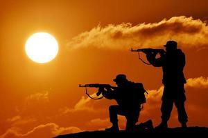 silhueta do soldado da equipe ou oficial com armas ao pôr do sol foto