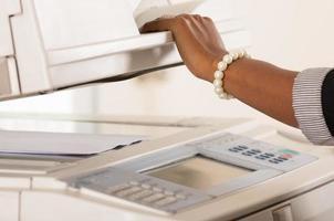 máquina de cópia de trabalho de mulher de escritório foto