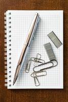 caneta no caderno com os clipes e grampos foto