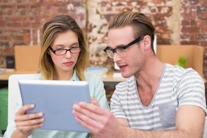 colegas usando tablet digital no escritório foto