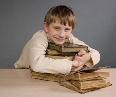 estudante de menino abraçando livros antigos foto