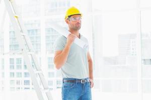 trabalhador manual segurando enrolado blueprint no escritório brilhante foto
