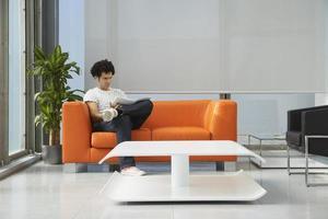 homem lê jornal no sofá laranja no escritório