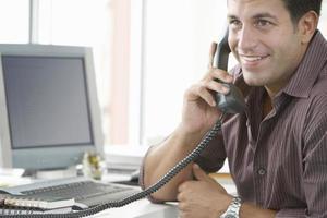 empresário feliz usando telefone fixo no escritório foto