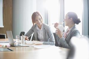 sorrindo jovens empresárias almoçando na mesa no escritório foto
