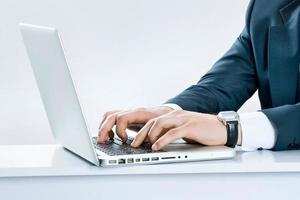 close-up de mãos masculinas, digitando no teclado do laptop foto