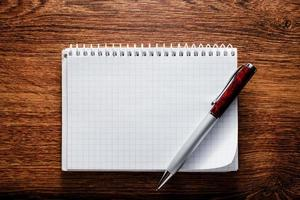 caderno aberto e caneta na mesa de madeira foto