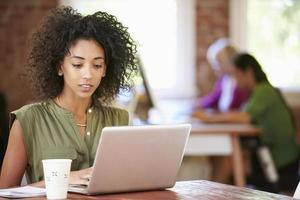 mulher que trabalha no laptop no escritório contemporâneo