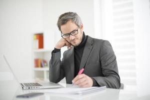arquiteto trabalhando em seu laptop no escritório foto