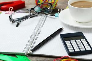 café e material de escritório em fundo cinza de madeira foto