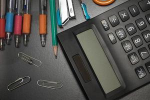 artigos de papelaria de escritório closeup em fundo preto, volta para shcool co foto