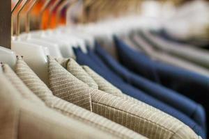 jaquetas elegantes penduradas na prateleira da loja foto