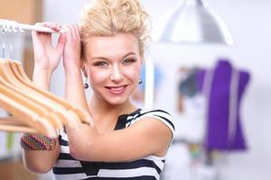 linda jovem estilista perto de prateleira com ganchos foto