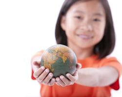 menina asiática segurando pequeno globo ou terra foto