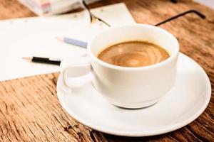 xícara de café e material de escritório na mesa de madeira velha foto