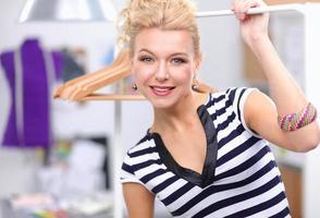 linda jovem estilista perto de prateleira com ganchos no escritório foto
