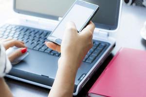 mãos de mulher com telefone inteligente e computador no escritório foto